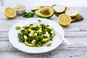 Fresh salad with kale leaves and avocado with pear on a white plate on wooden table.