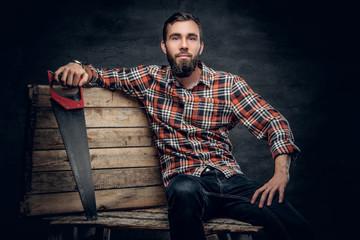 Bearded carpenter male holds handsaw.