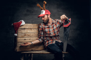 A bearded male in Christmas cap with deer horns holds handsaw.