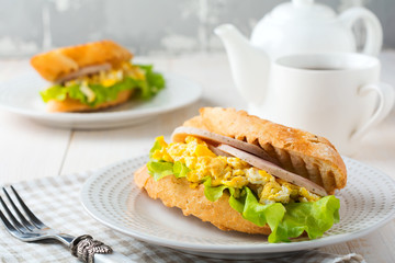 Sandwich stuffed with scrambled eggs, ham and lettuce leaves on a light wooden background. Selective focus.