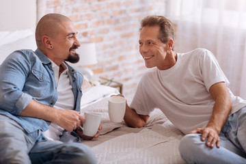 Delighted gay couple lying on the bed and drinking tea