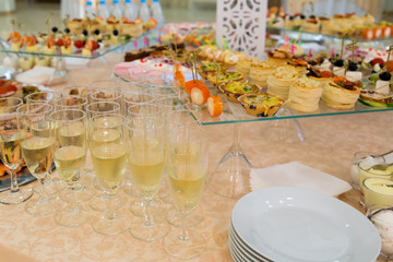 Banquet table with snacks, delicacies, beverages and desserts. On-site service. Catering