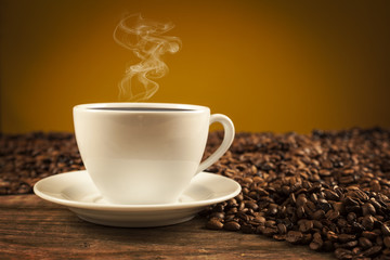 Porcelain cup of coffee on brown background