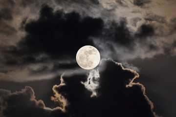 Supermoon with night sky and clouds.