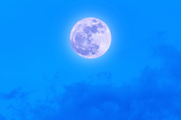Supermoon with blue sky and clouds.