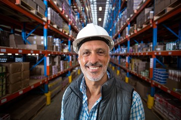 Portrait of smiling warehouse worker wearing hard hat