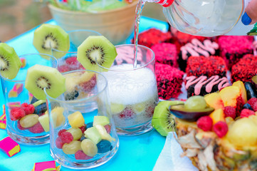 Champagne with fruit in a beautiful glass. Colorful Cakes on the occasion. Picnic table.