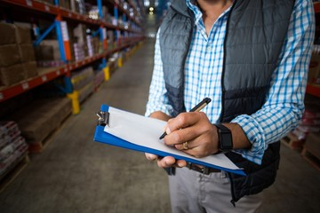 Mid section of warehouse worker writing on clipboard