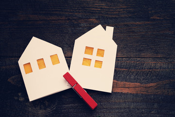 Two lodges from white paper on a wooden background. Symbol of the house, family, cosiness. Concept image house. Concept of sale or purchase house