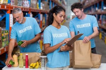 Volunteers packing eatables in cardboard box