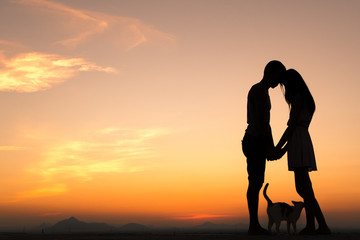 Silhouette of Happy Young Couple playing with cat Outside at Sunset