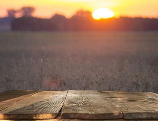 Empty wooden table over wheat field background,ripe corn ears