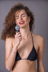 beautiful curly girl in a bikini singing into a microphone