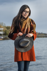 portrait of a girl in a hat and coat at the lake at sunset roman