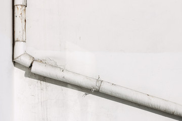 white plastered concrete wall with drain pipe