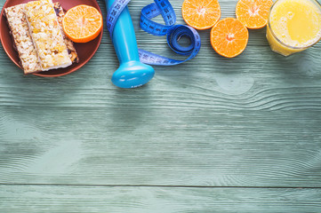 The concept of healthy lifestyle with copy space, top view. Orange juice, juicy citrus, cereal bars, dumbbell and measuring tape on green wooden table, flat lay. Diet and breakfast