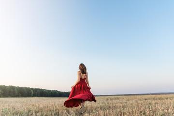 girl woman in red dress runs away on field