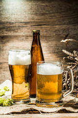 Mug, glasse, bottle of beer with foam on wooden background