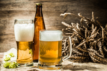 Beer mugs, glasses, bottle on cloth with hop ,wheat