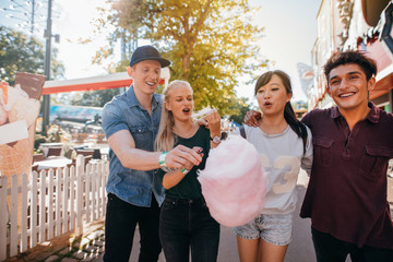 Friends eating cotton candy in amusement park
