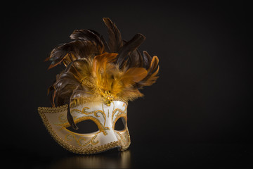 Pretty venician golden carnival mask with feathers isolated on a black background