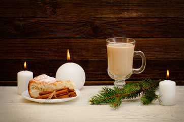 New Year`s mood, apple pie, cappuccino and spruce twigs on a wooden background