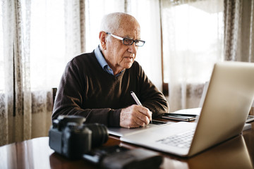 Senior photographer working with laptop at home