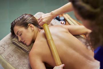 Woman enjoying massage with bamboo stick
