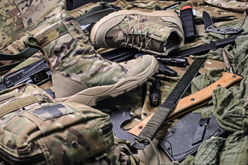 Pair of military boots/Pair of military boots, machete,ax,pistol and other military equipment.Top view.Selective focus