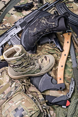 Different modern combat boots/Various army boots, ax, gun, knife, sunglasses and ammo.Top view.Selective focus