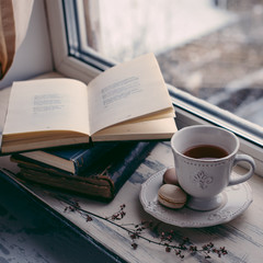 Cozy winter still life: cup of hot coffee and opened book on vintage windowsill against snow landscape from outside