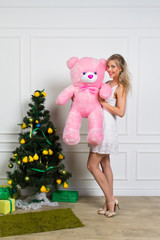Christmas portrait of happy girl with a teddy bear in his hands in a cozy interior on Xmas eve