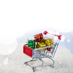 Shopping carts with Christmas gifts in the snow. Concept of Chri