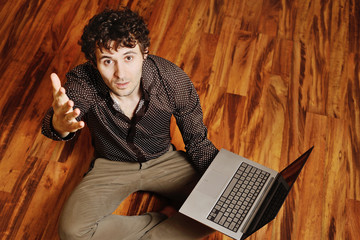 a young man with curly hair sits at a laptop on the warm floor. Creative idea, creator, designer