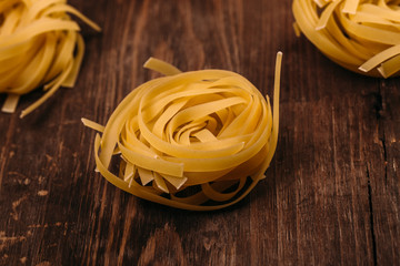 Uncooked rolled traditional italian pasta on wooden background, isolated. Portion of raw fettuccine or tagliatelle or pappardelle. Dry pasta from whole wheat flour. Ingredients for tasty dish
