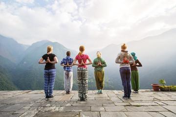 Group of people doing standing yoga exercise. Namaste behind the back, yoga asana on beautiful mountain landscape background