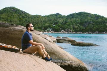 Male IT specialist in glasses sitting on sea beach enjoying outdoors