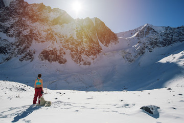 Young female with white dog travel in snow mountains, looking on sunrise, keeping photo camera in her hand