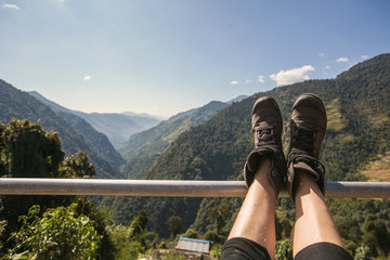Legs of traveler sitting on Himalaya high Mountains in travel. Freedom concept