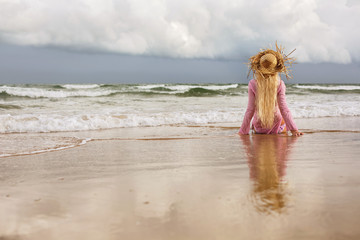 Blond woman sitting on sea shore, enjoy viewing ocean waves and beautiful clouds. Relax, freedom, summer vacation