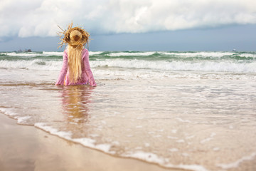 Blond woman in straw hat sitting on sea shore, enjoy summer, ocean waves and nature