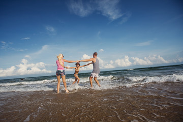 Happy young family having fun running on beautiful beach with waves and sea foam. Family traveling concept