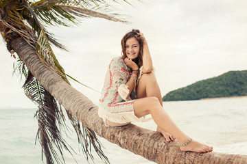 Happy young hippie girl sitting on palm tree on the beach on tropical island