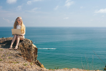 Attractive blonde hair woman working with a laptop on the seashore. Female freelancer working near the sea.