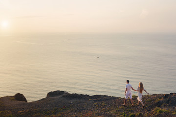 Love couple walking outdoor on  cliff near the beautiful ocean. Meeting the dawn. Sunrise
