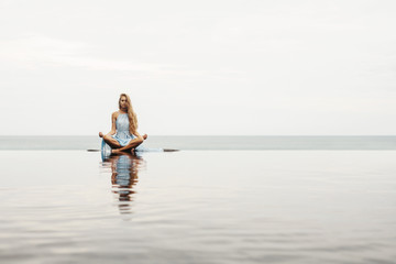 Beautiful female in blue dress sitting near sea beach in lotus pose, relax and meditate. Water Reflection in pool, woman practice