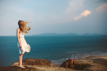 Young girl on rock beach, wind in blond hair and white dress