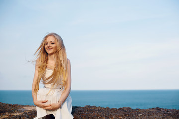 Portrait of happy smiling woman on the beach. Smiling Pretty blonde girl posing on beautiful wild beach