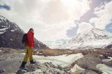 Mountaineer reaches of snowy mountain in a sunny day. Beautiful landscape, wild nature travel, Altai
