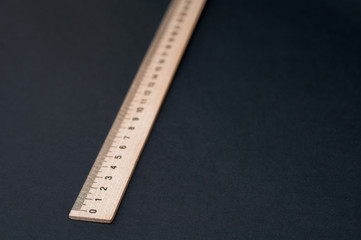 Long wooden ruler on a black background